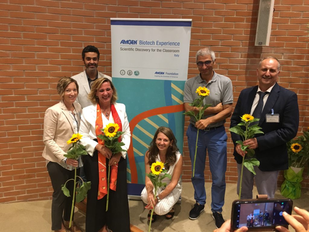 A group of ABE Italy educators and administrators pose for a photo holding sunflowers.