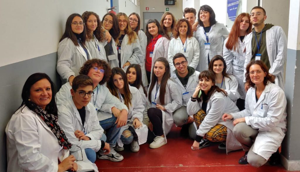 22 teachers and students from Pitagora High School in Pozzuoli, Italy, pose for a group photograph in the hallway of their school.
