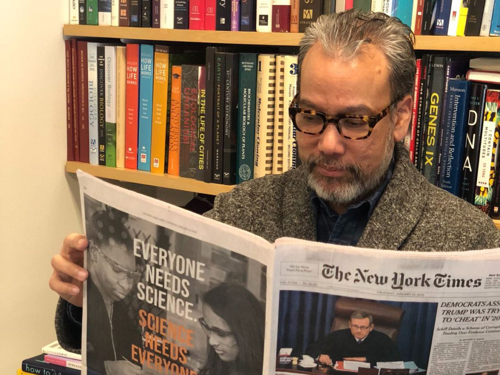 Robert Lue wearing glasses reads the New York Times newspaper