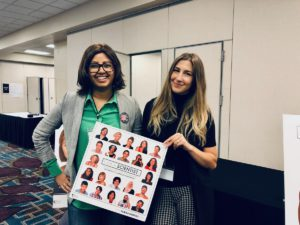 Two women pose for a photo with an I Am A Scientist poster